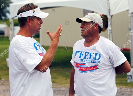 Stock Photo of New Orleans Saints head coach Sean Payton, left, and county music artist Sammy Kershaw, right, talk in between helping distribute food with 'Feed The Children' to families affected by the oil spill disaster in Venice, La