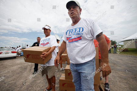 New Orleans Saints coach Sean Payton, left, and county musician Sammy Kershaw, right, help Feed the Children distribute food to families affected by the BP oil spill in Venice, La
