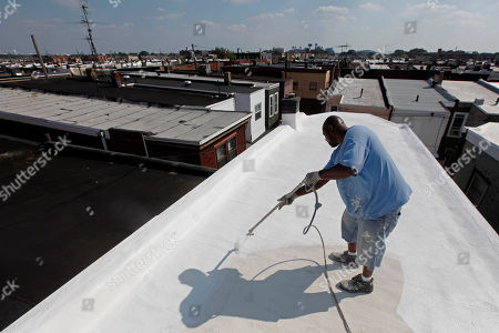 In this photo, James Peterson with Bio Neighbors, applies a coating of Acrymax to the roof of a row home in Philadelphia. The idea of painting roofs white has become something of a social movement, one that Energy Secretary (and Nobel Prize-winning physicist) Steven Chu believes could be a huge help in stopping global warming