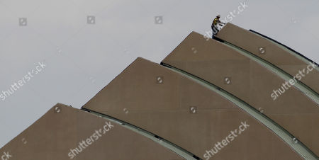 A worker stands on the roof of the Kauffman Center for the Performing Arts under construction in downtown Kansas City, Mo. . The center, designed by architect Moshe Safdie, is scheduled for completion in 2011