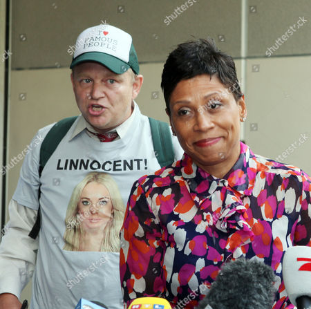 Lindsay Lohan's attorney Shawn Chapman Holley talks to reporters, as Jake Byrd, wears a T-shirt in support of Lohan, left, after Lohan was sentenced to jail, at the Beverly Hills courthouse, in Beverly Hills, Calif