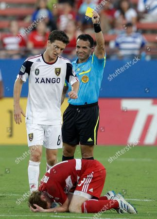 Hilario Grajeda, Will Johnson, Dax McCarty Referee Hilario Grajeda, rear, issues a yellow card to Real Salt Lake's Will Johnson (8) for sweepgin FC Dallas' Dax McCarty, bottom, in the first half of an MLS soccer match in Frisco, Texas