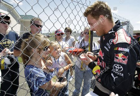 Stock Photo of Scott Speed Scott Speed signs an autograph for Zoe Sharp, 3, and her aunt Kaylee Martin during qualifying for the NASCAR Sprint Cup Series' Heluva Good! Sour Cream Dips at The Glen auto race in Watkins Glen, N.Y
