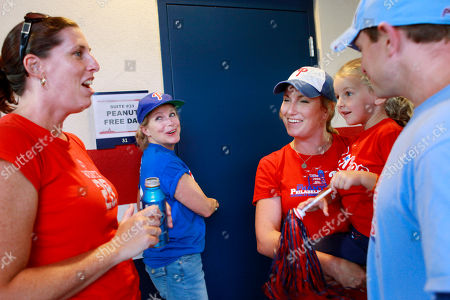 "This photo made, shows Jen Cole, of Frederick, Md., left, Ann Marie Cole, of Drexel Hill, Pa., center, and Mary Cole, of Wilmington, Del., holding her daughter, Catie Cole, 4, and Mike Cole, of Wilmington, Del., talk outside the ""peanut-free"" suite at Nationals Park, as the Philadelphia Phillies play against the Washington Nationals, in Washington. The large family attended with a teenage cousin whose peanut allergy keeps him from coming to most games"