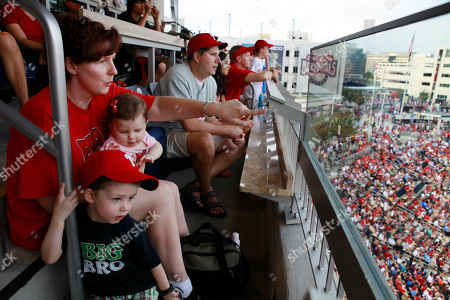 "This photo made, shows Jennifer Price, left, of Ellicott City, Md., her son Aidan Price, 4, who is allergic to peanuts, walnuts, cats and dogs, and daughter Teagan Price, 9 months, whose allergies are unknown, sitting in the ""peanut-free"" section of Nationals Park, as the Philadelphia Phillies play against the Washington Nationals, in Washington"