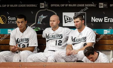 Mike Stanton, Cody Ross, Dan Uggla Florida Marlins Mike Stanton, left, Cody Ross (12) and Dan Uggla look on from the dugout during the ninth inning of a baseball game against the Colorado Rockies in Miami, . The Rockies won 10-0