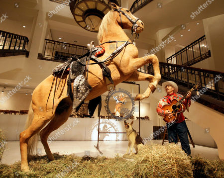 """Gil Perez Gil Perez, right, a doorman at Christies auction house, wears an outfit and holds a guitar belonging to Roy Rogers as he stands alongside the preserved remains of Rogers' horse """"Trigger"""" and dog """"Bullet"""" at the New York auction house, . Christie's held a preview Friday of an upcoming auction of items from the now-closed Roy Rogers and Dale Evans Museum in Branson, Mo"""