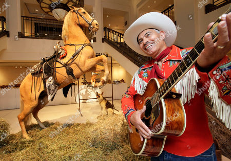 """Gil Perez The preserved remains of Roy Rogers' horse """"Trigger"""" and dog """"Bullet"""" are on display as Gil Perez, right, a doorman at Christies auction house, wears an outfit and holds a guitar belonging to Rogers, at the auction house in New York. A Nebraska cable TV network ponied up $266,500 for Roy Rogers' stuffed and mounted horse, Trigger, at an auction at Christie's in New York City on Wednesday July 14"""