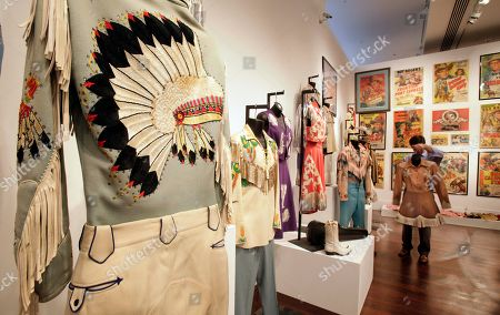 An employee of Christies auction house takes inventory of some of the belongings of movie cowboy Roy Rogers, in New York, . Christie's held a preview Friday of an upcoming auction of items from the now-closed Roy Rogers and Dale Evans Museum in Branson, Mo