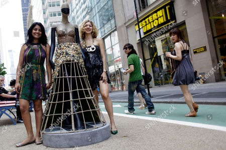 Designers Emily Saunders, right, and Niyati Karwat pose with their mannequin during the opening of the public art exhibit Fashion Center Sidewalk Catwalk, in New York. The exhibit features thirty-two custom-built mannequins that will spend the next three months on Broadway, each modeling a bold, one-of-a-kind manifestation of its designer's artistic vision