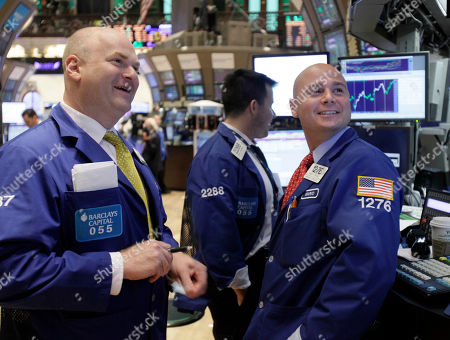 Specialists Evan Solomon, left, and Mario Picone, right, watch their screens at a post on the floor of the New York Stock Exchange, in New York