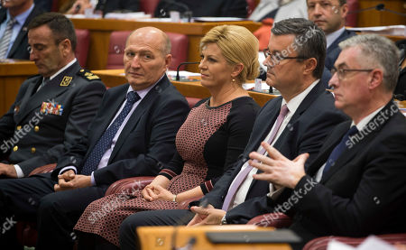 Croatian president Kolinda Grabar-Kitarovic, center and outgoing prime minister Tihomir Oreskovic, center right, attend a Parliament session in Zagreb, Croatia, . The ninth 151-member Croatian Parliament was inaugurated following the Sept. 11, 2016 snap election