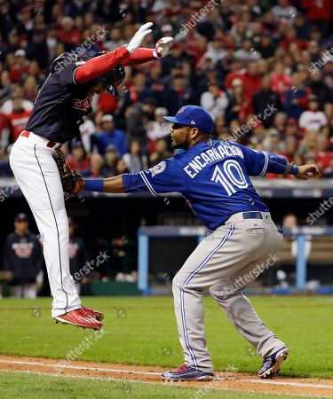 Toronto Blue Jays first baseman Edwin Encarnacion, right, tags out Cleveland Indians' Coco Crisp during the seventh inning in Game 1 of baseball's American League Championship Series in Cleveland
