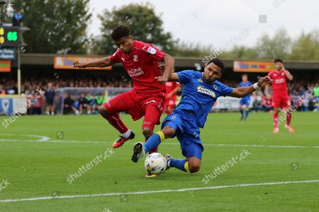 AFC Wimbledon striker Andy Barcham (17) and Swindon Town midfielder John Goddard (10) tussle during the EFL Sky Bet League 1 match between AFC Wimbledon and Swindon Town at the Cherry Red Records Stadium, Kingston