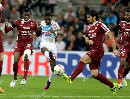 Bouna Sarr, Benoit Assou-Ekotto, Opa Nguette Marseille's Bouna Sarr, left, challenges for the ball with Metz's Benoit Assou-Ekotto, right, and Opa Nguette during the French League One soccer match between Marseille and Metz, at the Velodrome Stadium, in Marseille, southern France