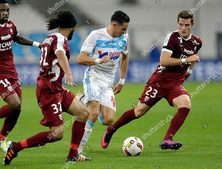 Florian Thauvin, Chris Philipps, Benoit Assou-Ekotto Marseille's Florian Thauvin, center, challenges for the ball with Metz's Chris Philipps, right, and Benoit Assou-Ekotto during the French League One soccer match between Marseille and Metz, at the Velodrome Stadium, in Marseille, southern France