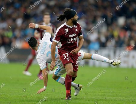 Stock Picture of Florian Thauvin, Benoit Assou-Ekotto Marseille's Florian Thauvin, behind, challenges for the ball with Metz's Benoit Assou-Ekotto during the French League One soccer match between Marseille and Metz, at the Velodrome Stadium, in Marseille, southern France