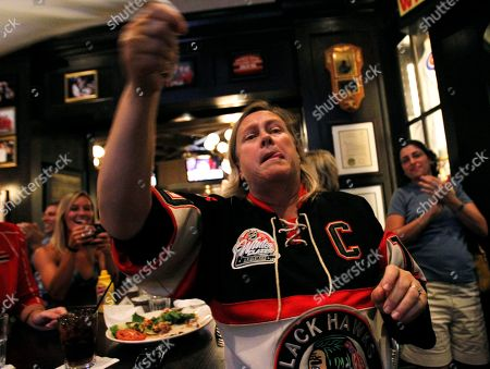 A Chicago Blackhawks fan celebrates after the Blackhawks score in the second period against the Philadelphia Flyers during Game 6 of the NHL Stanley Cup hockey finals at Harry Caray's Tavern Navy Pier in Chicago