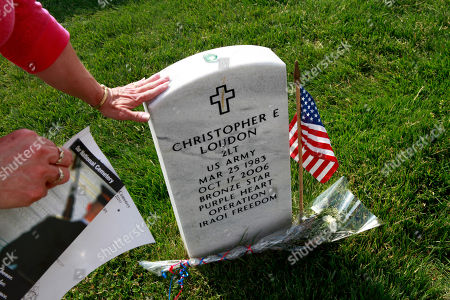 Katie Echols, of Leavenworth, Kan., touches the grave of Army 2nd Lt. Christopher Loudon, who died while serving in Iraq along with Echols' grandson, Army Corp. David Unger, 21. Though Unger is buried in Kansas, Echols wanted to visit the graves in section 60 of Arlington National Cemetery, where many of the casualties from Iraq and Afghanistan are buried, among flags placed in preparation of Memorial Day in Arlington, Va., on