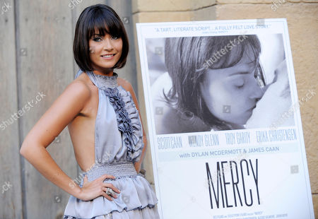 """Wendy Glenn Wendy Glenn, a cast member in the film """"Mercy,"""" poses alongside the poster for the film at the premiere of the film in Los Angeles"""