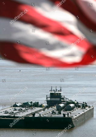 "Barges are pushed by the towboat ""Linda Taylor"" near a large flag at Murray Lock and Dam in Little Rock, Ark"