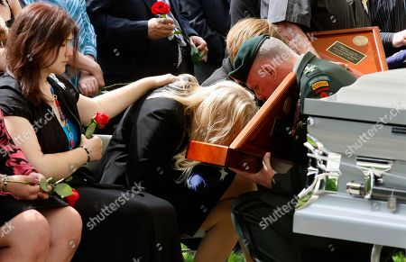 Mary McCraw, Eileen Daly, John Mulholland Mary McCraw, left, reaches out as her mother, Eileen Daly, cries over a folded flag presented by U.S. Army Lt. Gen. John Mulholland, right, during the funeral service, in Wrightstown, N.J., for Daly's son and McCraw's brother, U.S. Army Sgt. Ronald Alan Kubik, 21, of Brielle, N.J. Kubik was killed in action April 23, 2010, in Logar Province, Afghanistan