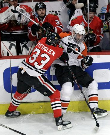 Dustin Byfuglien, Ian Laperriere Chicago Blackhawks right wing Dustin Byfuglien (33) checks Philadelphia Flyers center Ian Laperriere into the boards in the first period of Game 2 of the NHL hockey Stanley Cup finals, in Chicago