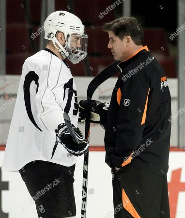 Philadelphia Flyers head coach Peter Laviolette, right, talks with center Ian Laperriere, left, during practice, in Chicago. The Chicago Blackhawks are scheduled to play the Philadelphia Flyers in Game 2 of the Stanley Cup hockey finals on Monday. The Blackhawks lead the series 1-0