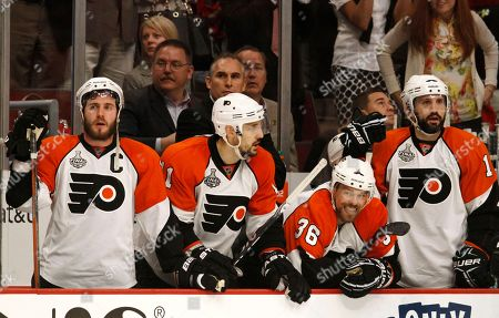 Philadelphia Flyers players Mike Richards, left, Blair Betts (11), Darroll Powe (36), and Ian Laperriere, right, watch the final moments of the third period of Game 5 against the Chicago Blackhawks in the NHL Stanley Cup hockey finals, in Chicago. The Blackhawks won 7-4 and lead the series 3-2
