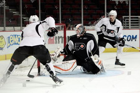 Philadelphia Flyers goalie Johan Backlund, of Sweden, center, practices with Darroll Powe, left, and Ian Laperriere, right,, in Chicago. The Chicago Blackhawks are scheduled to play the Flyers in Game 2 on Monday