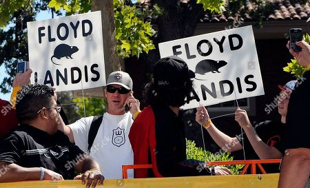 Fans hold up signs about Floyd Landis during the final stage of the Tour of California cycling race, in Thousand Oaks, Calif. Landis recently admitted to using performance enhancing drugs, and made doping allegations against seven-time Tour de France winner Lance Armstrong