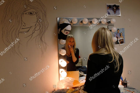 "Terri Colombino With only four bulbs in her make-up mirror still burning because ""there are no funds to replace them,"" cast member Terri Colombino applies lipstick in in her dressing room during the final weeks of taping for CBS's soap opera ""As the World Turns,"" at JC Studios in New York, . The final episode of the soap opera, which has been running since 1956, will air on Sept. 17. Colombino has been on the show since 1999"
