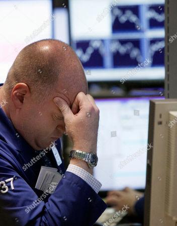 Evan Solomon Specialist Evan Solomon rubs his brow as he works on the floor of the New York Stock Exchange, in New York