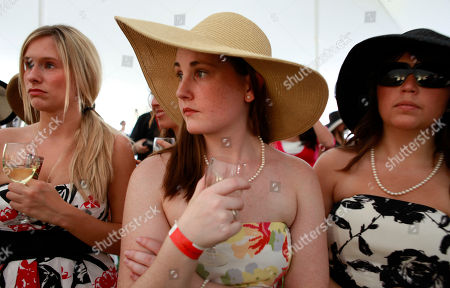 Kara Toth, left, Allison Broemel, both of Arlington, Va., and Sarah Simmons, of McLean, Va., watch the opening ceremonies America's Polo Cup Championships by the National Mall in Washington, on . The event was hosted by White House party crashers Tareq and Michaele Salahi