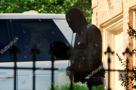 Washington Wizards basketball player Gilbert Arenas pulls the strings of a sweatshirt tight to obscure his face after arriving at his home in Great Falls, Va.,, after being released from a halfway house where he served part of his sentence for bringing guns into the Washington Wizards locker room