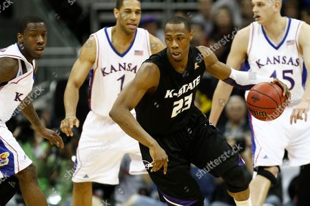 Dominique Sutton, Tyshawn Taylor, Xavier Henry, Cole Aldrich Kansas State's Dominique Sutton (23) looks to pass in front of Kansas defenders Tyshawn Taylor, left, Xavier Henry (1) and Cole Aldrich, right, during the second half of an NCAA college basketball championship game at the Big 12 Conference men's tournament, in Kansas City, Mo. Kansas won 72-64