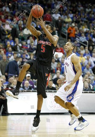 D'walyn Roberts, Xavier Henry Texas Tech forward D'walyn Roberts (5) drives to the basket past Kansas guard Xavier Henry during the first half of an NCAA college basketball game at the Big 12 Conference men's tournament, in Kansas City, Mo
