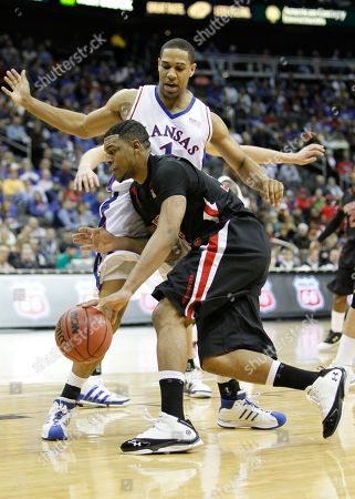 Mike Singletary, Xavier Henry Texas Tech forward Mike Singletary drives past Kansas guard Xavier Henry, rear, during the first half of an NCAA college basketball game at the Big 12 Conference men's tournament, in Kansas City, Mo