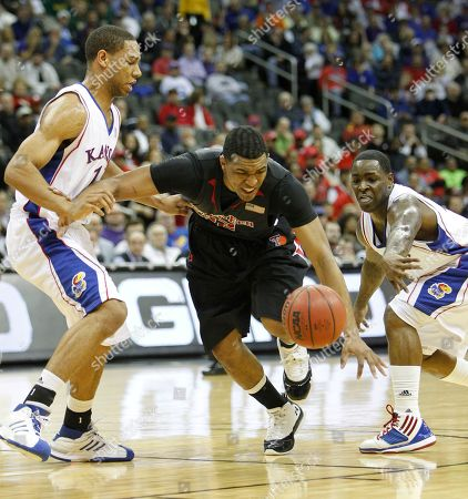 Mike Singletary, Xavier Henry, Sherron Collins Texas Tech's Mike Singletary, center, drives between Kansas' Xavier Henry, left, and Sherron Collins, right, during the first half of an NCAA college basketball game at the Big 12 Conference men's tournament, in Kansas City, Mo