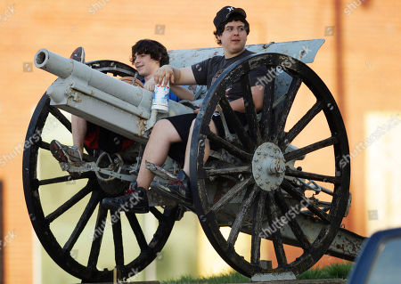 Stock Photo of Brett Cooper, left and Dakota Blount sit on a cannon in front of the Chase County Courthouse, in Cottonwood Falls, Kan