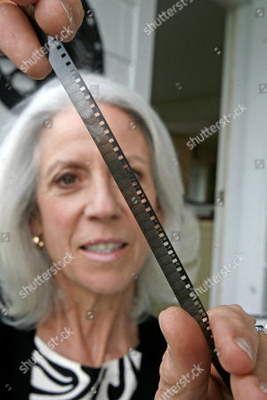 "Stock Image of Susan Cooke Kittredge holds an 8mm home movie made by her father, Alistair Cooke, in Shelburne, Vt. More than 75 years after it was filmed, a home movie of Charlie Chaplin shot by a young journalist named Alistair Cooke is getting its first public viewings. ""All At Sea,'' an 11-minute black-and-white filmed on a 1933 boating trip that inclluded Chaplin, Paulette Goddard and a 24-year-old Cooke, shows Chaplin miming Greta Garbo, the Prince of Wales and Napoleon. It was discovered among Cooke's belongings after his 2004 death and is getting its first U.S. showings in Vermont, where his daughter lives"