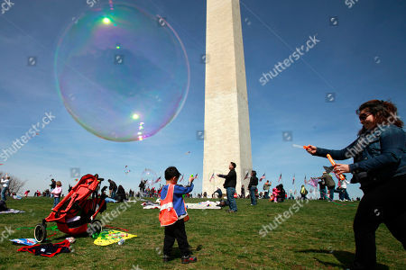 Stock Photo of Claudia Sandoval Wright, right, of Alexandria, Va., blows soap bubbles for children to catch by the Washington Monument on the opening day of the National Cherry Blossom Festival in Washington, on