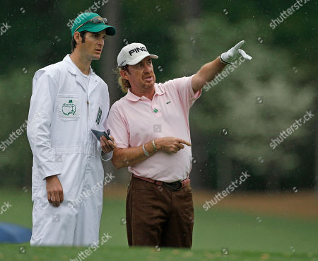 Miguel Angel Jimenez of Spain chats with his caddie Mike Hough on the 12th tee during the first round of the Masters golf tournament in Augusta, Ga