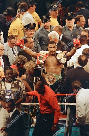 Mike Tyson Undisputed heavyweight world champ Mike Tyson shows off his belts following his first round knockout of Michael Spinks in their title bout in Atlantic City, Monday, July 1988