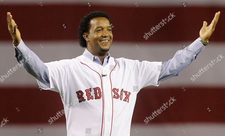 Former Boston Red Sox pitcher Pedro Martinez greets the crowd before throwing the ceremonial first pitch before the opening game of the baseball season between the Red Sox and New York Yankees, in Boston. Martinez will serve as a studio analyst for TBS during the baseball playoffs. The network said, that the three-time Cy Young Award winner will join host Keith Olbermann
