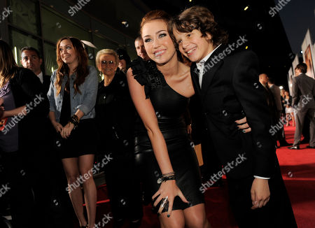 """Stock Photo of Miley Cyrus, Bobby Coleman Miley Cyrus, a cast member in """"The Last Song,"""" poses with fellow cast member Bobby Coleman, right, on the red carpet at the premiere of the film in Los Angeles"""
