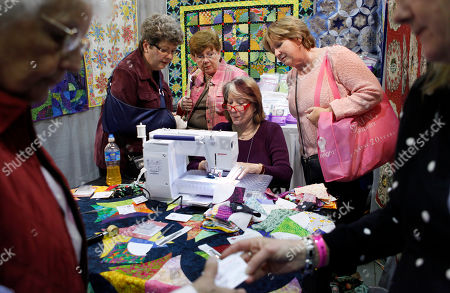 Sandra Chandler, of Hunt, Texas, seated at the sewing machine, creator of the Curve Master Presser Foot, demonstrates the sewing machine quilting tool to Alice Riles, of Dover, Del., left standing, Stacey Abernethy, also of Dover, center standing, and Lisa Shepherd, of Los Angeles, right standing, during the American Quilter's Society Quilt Show and Contest at the Lancaster County Convention Center in Lancaster, Pa., . The show runs through March 27