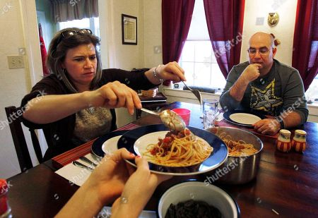"""Stock Picture of In this photo, U.S. Army Maj. Jeff Hall, right, has dinner with his wife Sheri, left, and daughter Tami at their home at Fort Riley, Kan. It was after his first tour, when his family was having dinner at a restaurant and one of his daughters refused to touch her steak because sour cream had gotten on it. Hall began crying. His family was stunned. What Hall didn't reveal was his daughter's fussiness had dredged up memories of a family in Iraq that would regularly get propane at a station he had guarded. Their two girls, close to his daughters' ages, were so emaciated their skin hung like loose cloth. """"I could just see the faces of the little girls"""