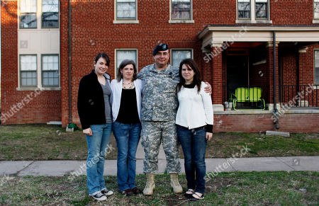 In this photo, U.S. Army Maj. Jeff Hall poses with his family, from left, daughter Tami, wife Sheri, and daughter Courtney, outside their post housing at Fort Riley, Kan. Hall's world imploded after his second tour in Iraq. Overwhelmed with guilt and rage, the 18-year Army veteran became so depressed that one day he lay on the ground and pointed a pistol at his head. Nearly 300,000 troops have served three, four or more times. And, records show, more than half of those currently at war are at least on their second tour