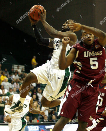 Charlotte's An'Juan Wilderness, left, drives to the basket past Massachusetts Ricky Harris during the first round of the NCAA college Atlantic 10 men's basketball championship in Charlotte, NC